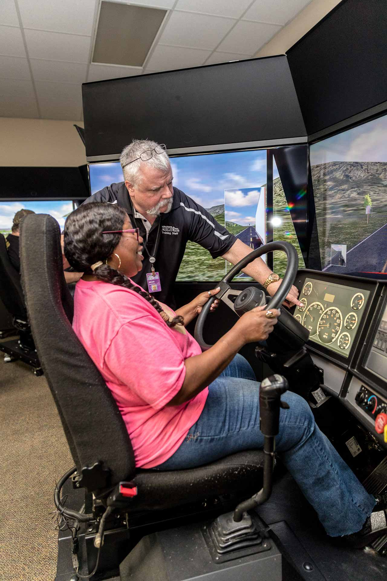 A Prime driving instructor showing a student driver something during a driving simulation.
