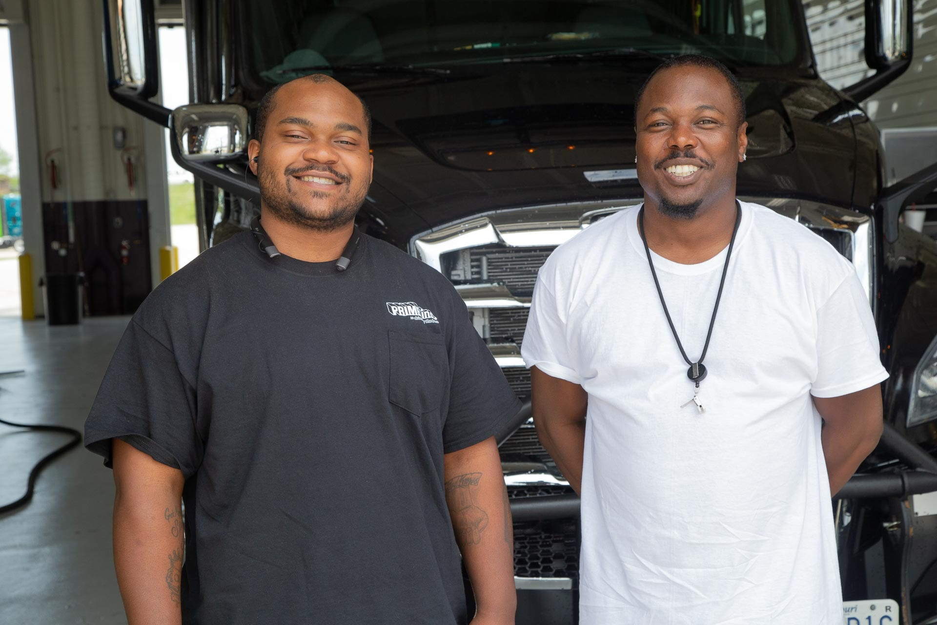 Two Prime truck drivers posing for a picture in front of a black Freightliner semi-truck.