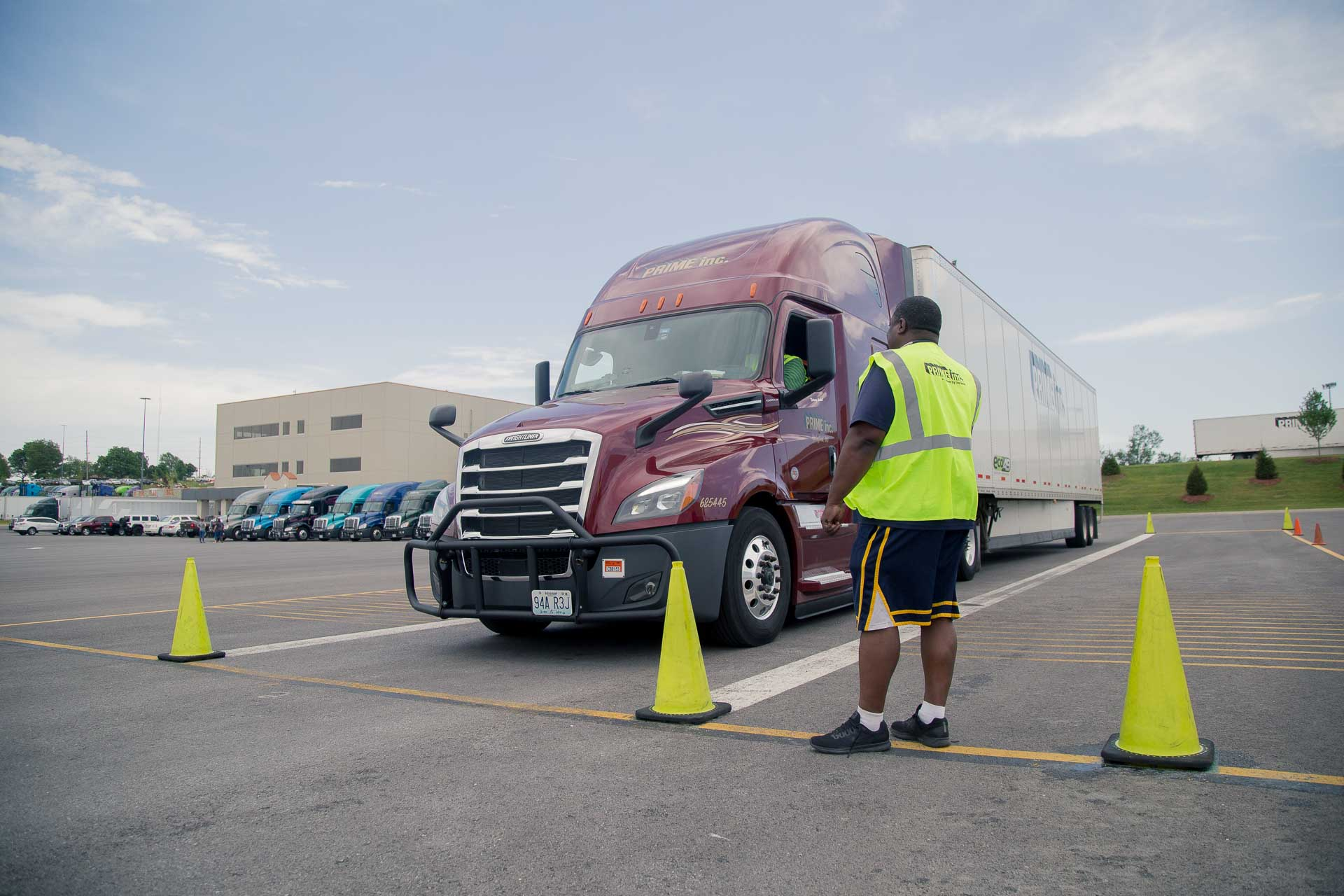 A Prime driving instructor observing a student driver in a red semi-truck driving in a parking lot.