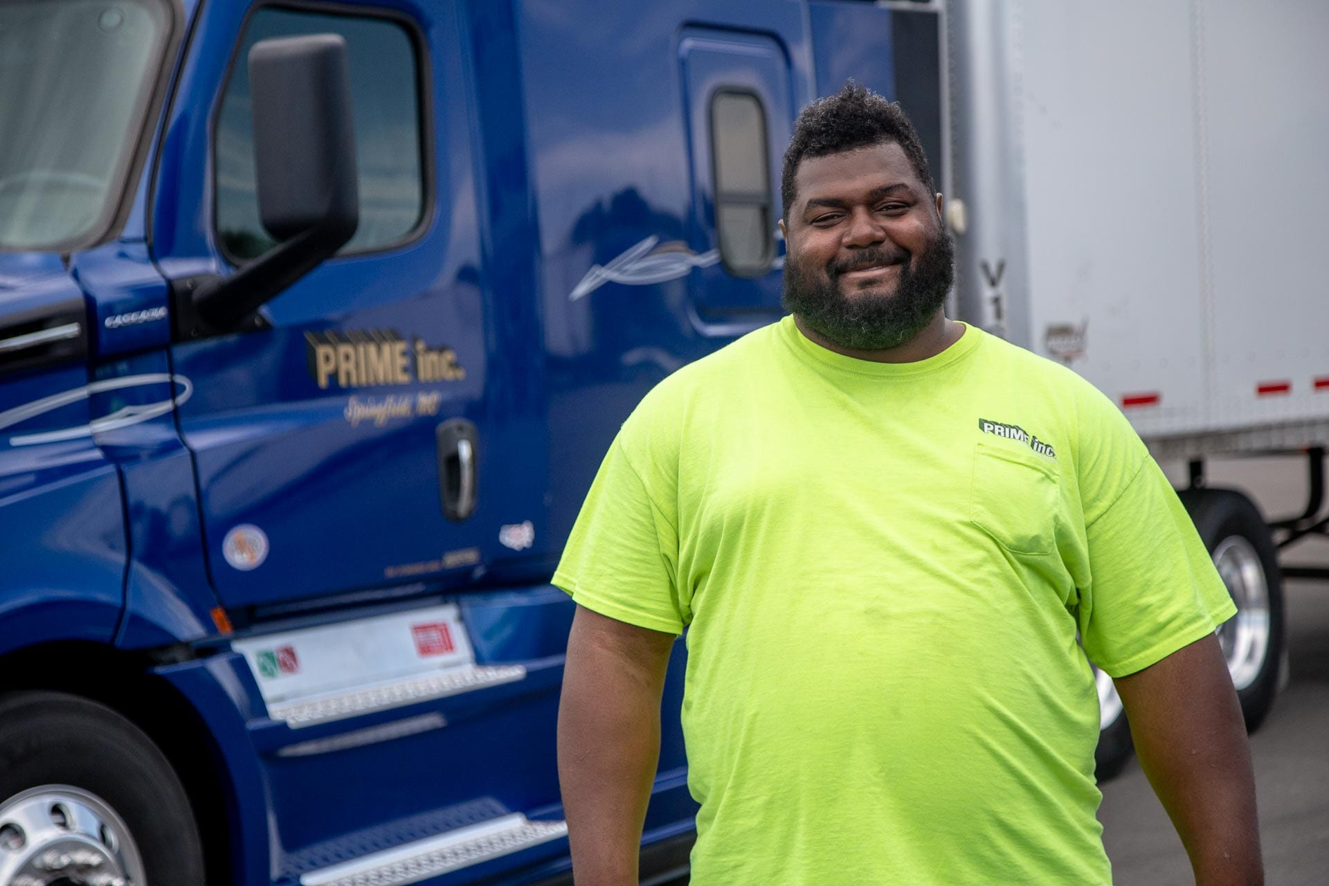 A Prime truck driver, wearing a safety yellow t-shirt, standing in front of a dark blue semi-truck.
