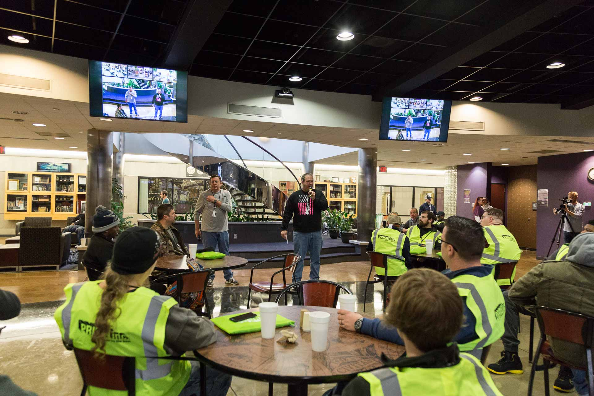 A Prime Inc. associate speaking to his team in a cafeteria area who are all wearing bright green safety vests.