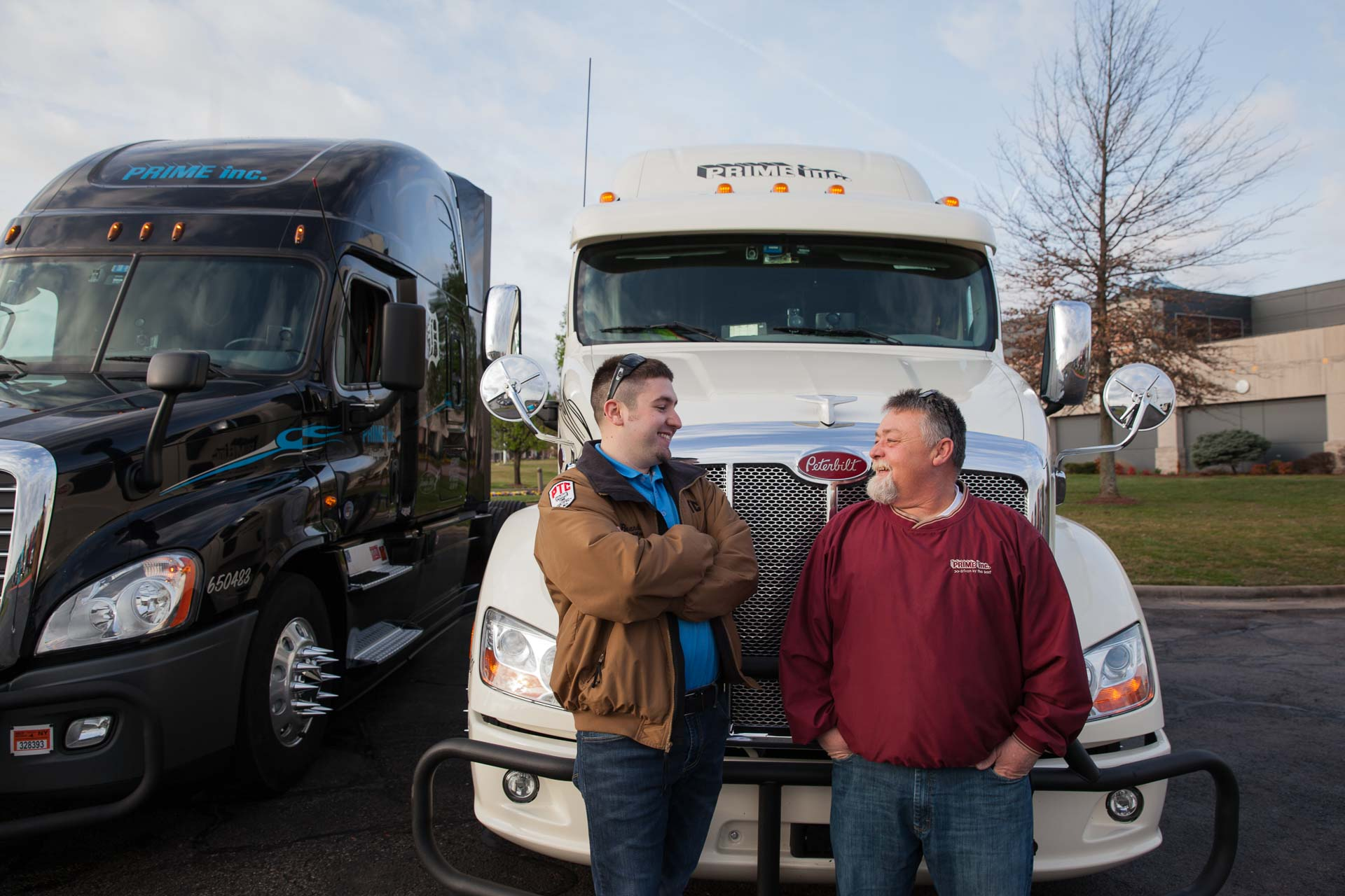 A team of Prime truck drivers talking in front of their newly leased semi-truck.