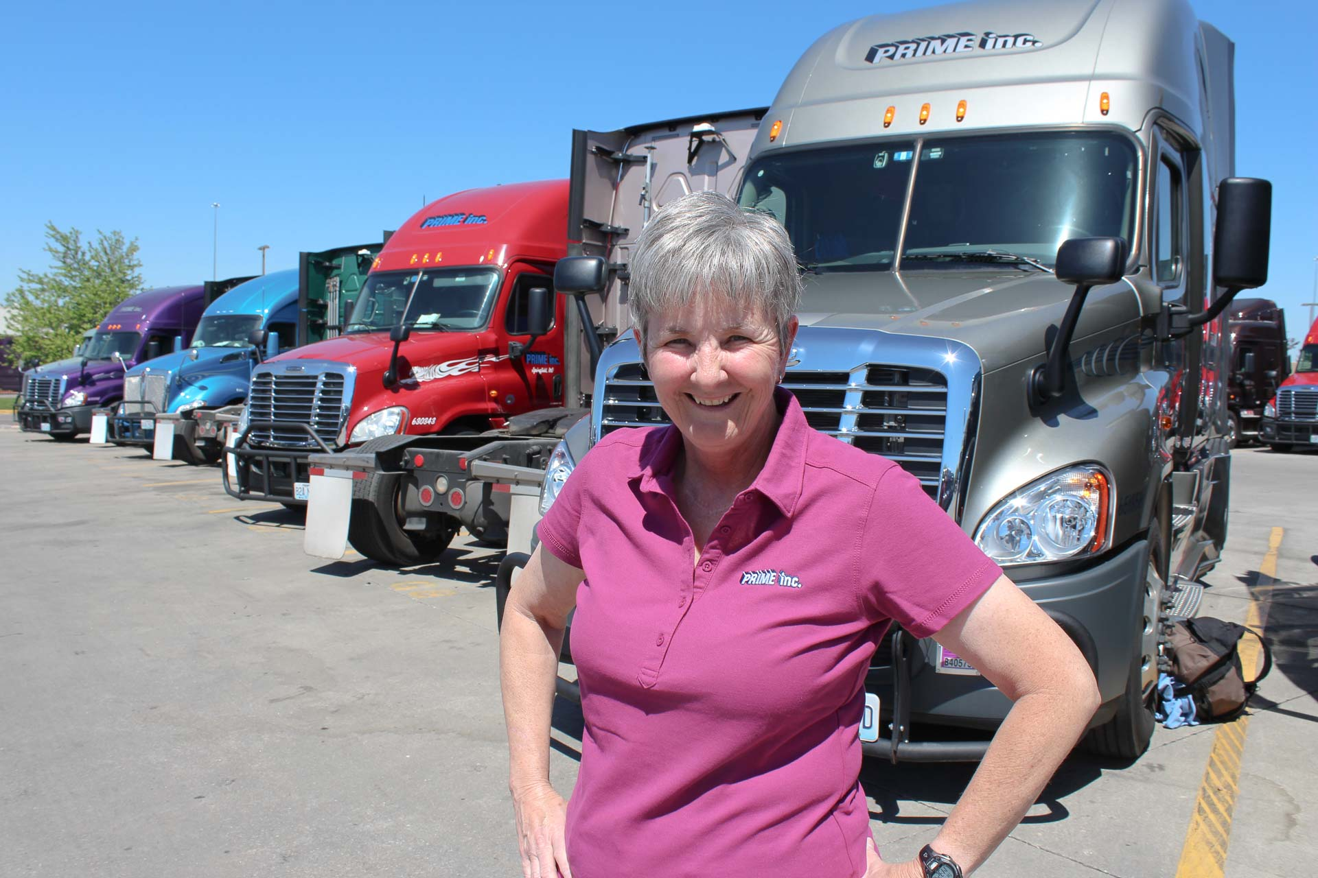 Reba Hoffman, a female truck driver at Prime, standing in front of a row of Freightliner semi-trucks.