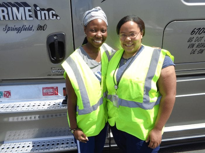 Two of Prime Inc's female truck drivers, standing in front of a brown semi-truck, wearing bright yellow safety vests.