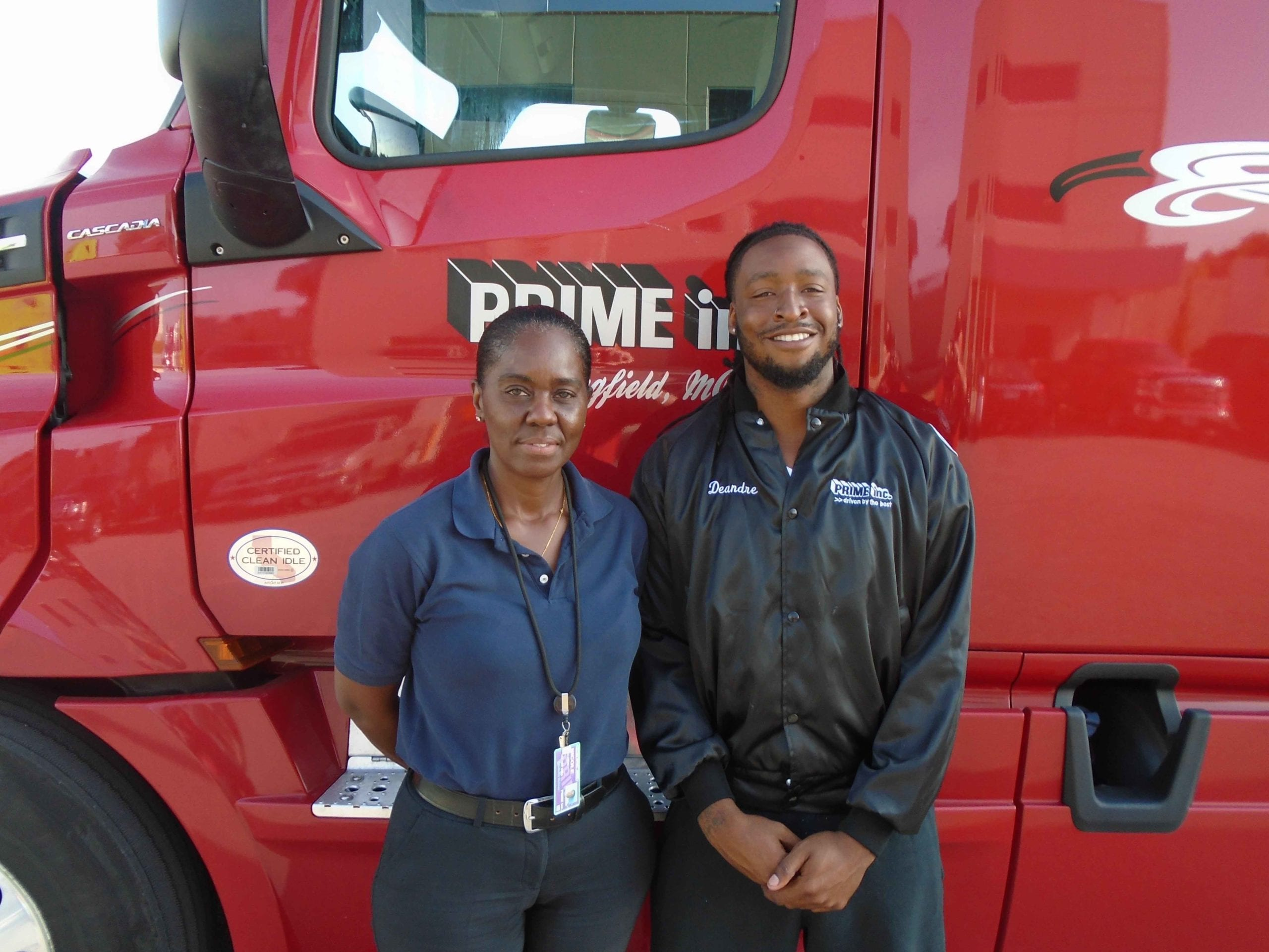 Deandre, a Prime student truck driver. standing with his instructor in front of a red semi-truck.