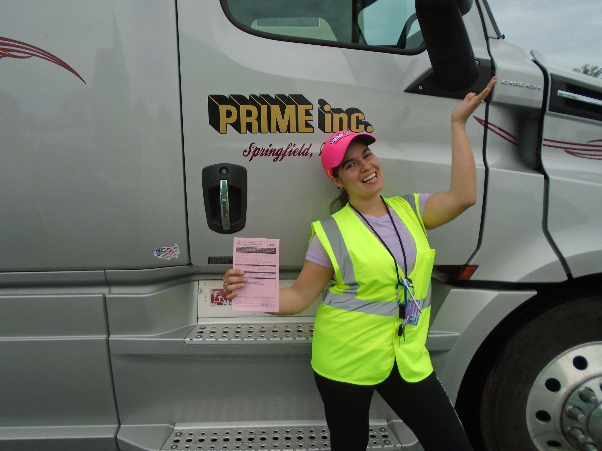 A Prime, Inc. female truck driver, wearing a bright safety vest and a pink hat, standing in front of a brown semi-truck while holding up her CDL exam scores.