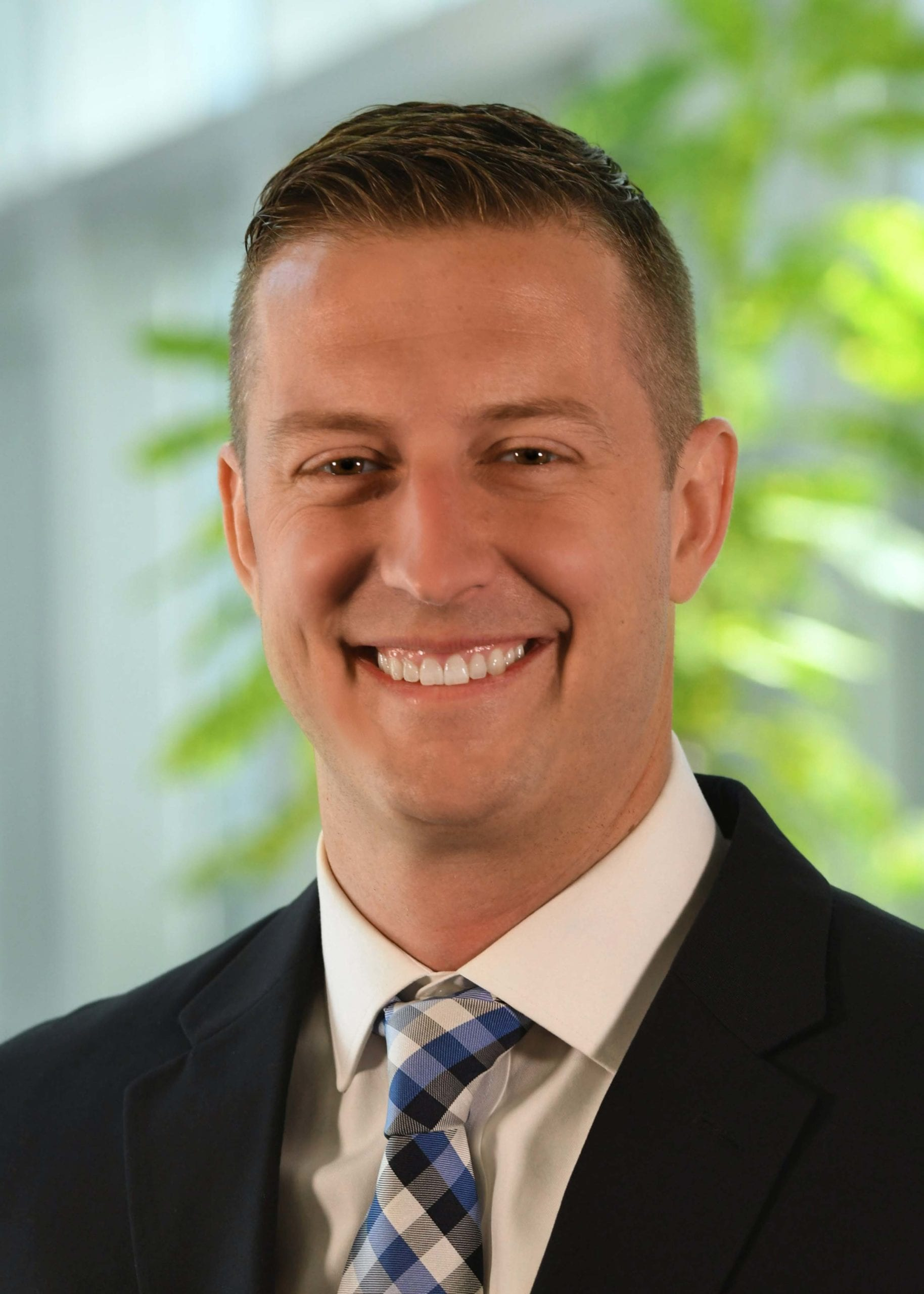 Prime's Recruiting Manager Travis Bacon, smiling while wearing a black suit with a blue & black tie.